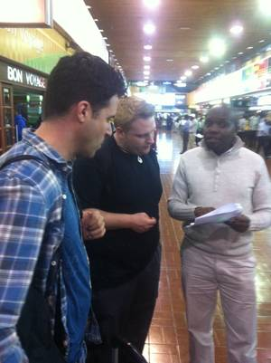 Frankie and Ricky Moreno at the Nairobi airport, discussing logistics with a driver named Dennis.