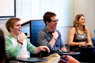 Iowa students Storm Vaske (from left),.Drew O'Bleness, and Chelsea Gaylord crack up laughing while collectively sharing daily stories with their classmates during their morning meeting for their college course
