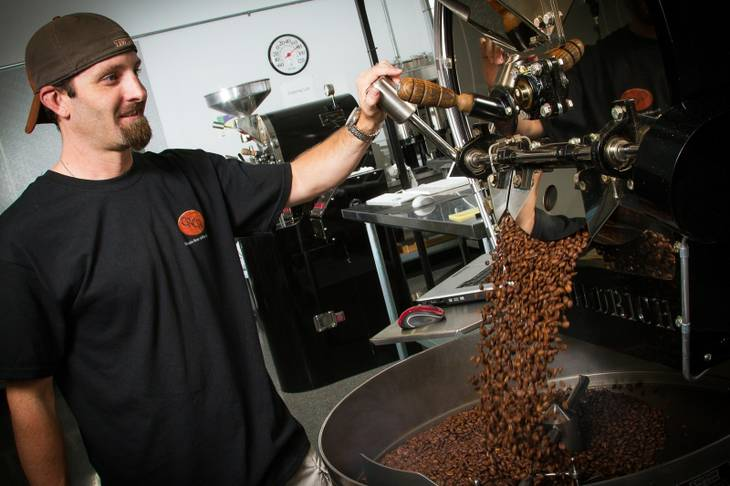 Colorado River Coffee Roasters buys raw coffee beans from importers, roasts them on site and packages and distributes them to cafes, restaurants and retailers. Above, roaster Erik Anderson processes beans at the company's Boulder City headquarters.