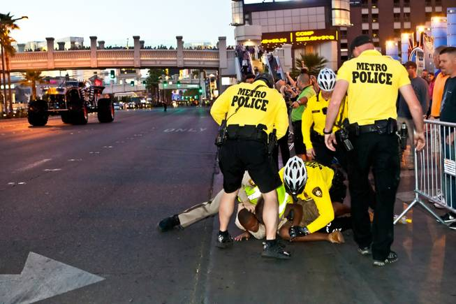 Las Vegas Metropolitan Police take down a spectator as he tried to run into the street to get a closer look at the monster trucks as the parade of 11 Champions of Advance Auto Parts Monster Jam SM World Finals travels down Las Vegas Boulevard Thursday night, March 21, 2013.
