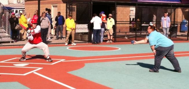 A Miracle League player prepares to hit an incoming pitch.