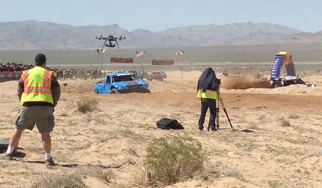 A crew uses cameras mounted on a tripod and an aerial drone to capture action from the Mint 400 off-road race Saturday, March 23, 2013, near Las Vegas.