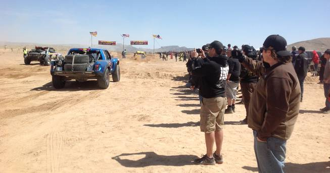 Fans line the course of the Mint 400 off-road race Saturday, March 23, 2013, near Las Vegas.
