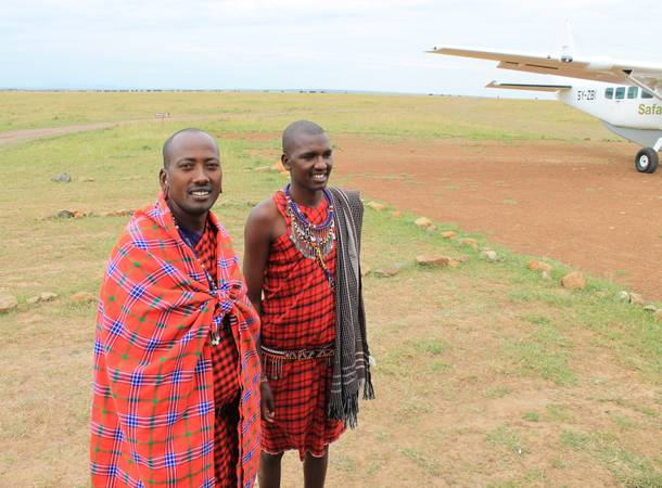 Porini Mara Camp employees Geoffrey Risa Ketere and Ripa Olmara greet a party of visitors at the Ol Kinyei Conservancy airfield.