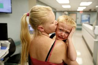 Angela comforts her son Kaleb as they leave University Medical Center in Las Vegas, where they were visiting Kaleb's dad Tom, on Thursday, March 28, 2013. According to the National Center of Family Homelessness, there are over 1500 children homeless in Nevada.