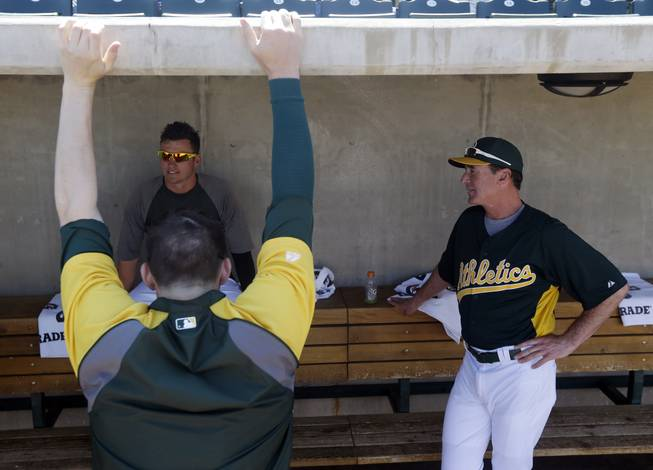 Oakland Athletics manager Bob Melvin, right. talsk to Josh Donaldson, left facing camera, and Jarrod Parker before an exhibition spring training baseball game against the Seattle Mariners on Monday, March 18, 2013 in Phoenix.