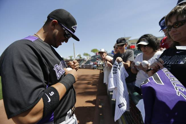 Colorado Rockies left fielder Carlos Gonzalez signs autographs before playing the Kansas City Royals in an exhibition spring training baseball game Tuesday, March 19, 2013, in Surprise, Ariz.