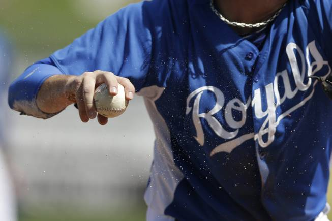 Chalk from the third base line flies as Kansas City Royals third baseman Mike Moustakas grabs a ground ball against the Colorado Rockies during the third inning in an exhibition spring training baseball game Tuesday, March 19, 2013, in Surprise, Ariz.
