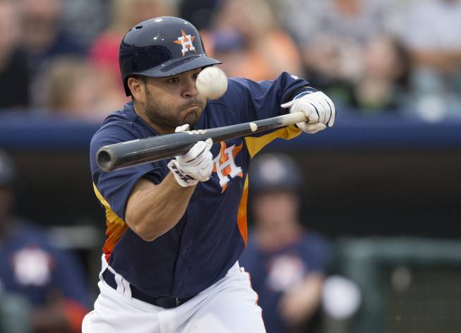 Houston Astros' Jose Altuve attempts to bunt for a base hit during the second inning of an exhibition spring training baseball game against the New York Mets on Wednesday, March 20, 2013, in Kissimmee, Fla.