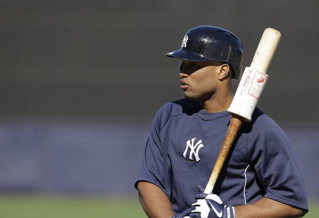 New York Yankees second baseman Robinson Cano warms up with a weight on his bat before a spring training baseball game in Tampa, Fla., March 21, 2013.