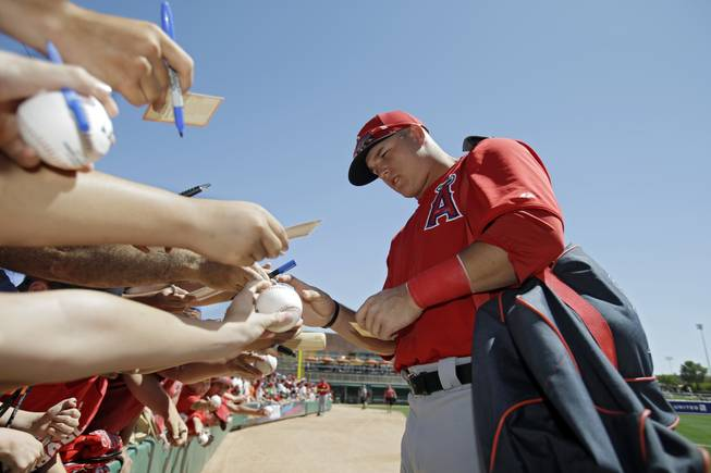 Los Angeles Angels' Mike Trout signs for fans before an exhibition spring training baseball game against the Chicago White Sox Monday, March 25, 2013, in Glendale, Ariz.