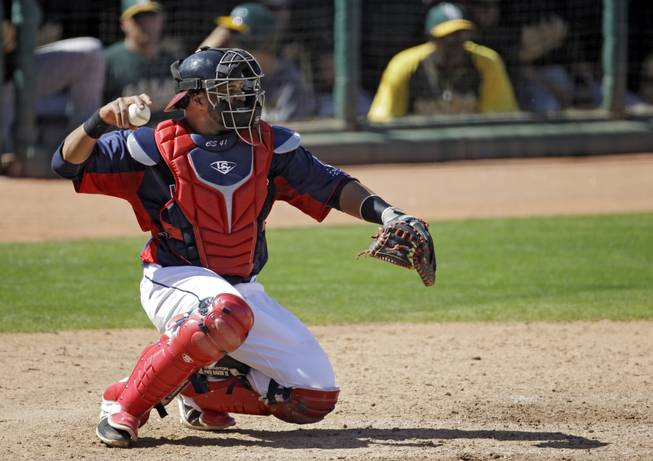 Cleveland Indians catcher Carlos Santana warms up his pitcher in an exhibition spring training baseball game against the Oakland Athletics Tuesday, March 26, 2013, in Goodyear, Ariz.