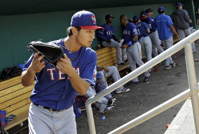 Texas Rangers starting pitcher Yu Darvish leaves the dugout to start the bottom of the fifth inning in an exhibition spring training baseball game against the Cincinnati Reds Saturday, March 23, 2013, in Goodyear, Ariz.