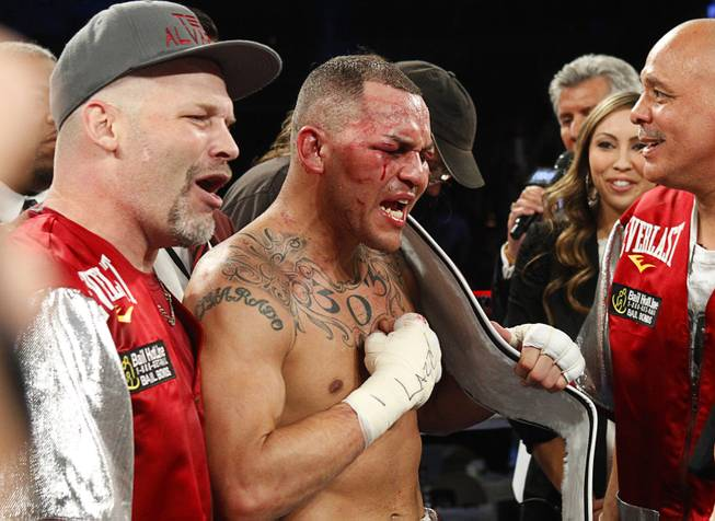 Mike Alvarado, center, celebrates his victory over Brandon Rios following a super lightweight bout for an interim 140lb. WBO title at the Mandalay Bay Events Center Saturday, March 30, 2013. The fight was a rematch to a Oct. 13, 2012 fight  which Rios won.