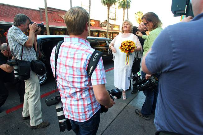 "Nancy Levandowski has a wireless mic fitted by a crew from the television tabloid show ""Inside Edition"" before she exchanges wedding vows with Steve Keller at the Denny's restaurant on Fremont Street Wednesday, April 3, 2013."