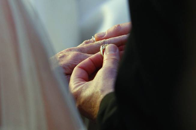 Steve Keller places a ring on Nancy Levandowski's finger as they exchange wedding vows at the Denny's restaurant on Fremont Street Wednesday, April 3, 2013.