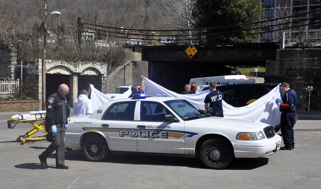 Law enforcement officers and emergency service personnel cover the vehicle at the scene of the shooting in downtown Williamson, W.Va., Wednesday, April 3, 2013, where Sheriff Eugene Crum was shot and killed at point blank range.