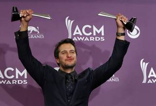 Luke Bryan holds his awards for Entertainer of the Year and Vocal Event of the Year at the 48th Annual Academy of Country Music Awards at MGM Grand on Sunday, April 7, 2013.