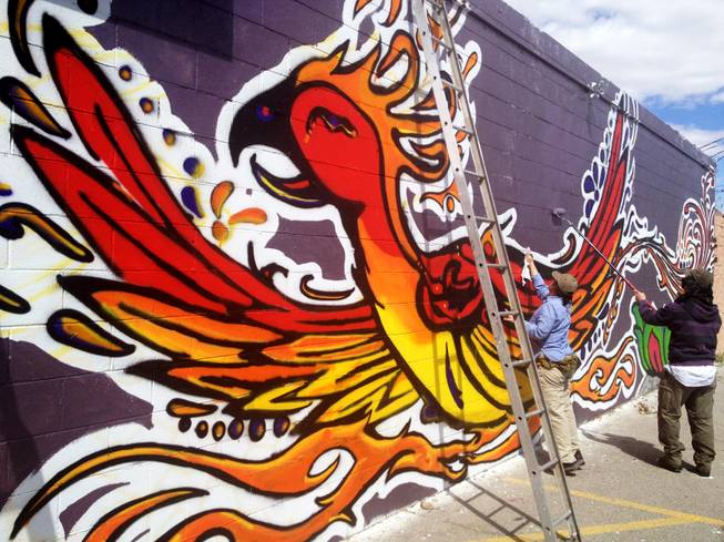Garrison and Alison Buxton of Londonderry, Vt., add the finishing touches to a mural on the rear of the Huntridge Theater in downtown Las Vegas. The mural of a phoenix gives rise to suggestions the theater may be undergoing a rebirth.