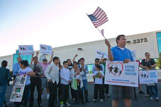 Martin Martinez, who is fighting for a petition for residency in the United States, stands with a large group of protesters in front of a local ICE office demanding action on immigration reform, Wednesday April 10, 2013.