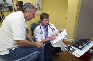 Gerry Eirkl of Henderson looks over a list of providers with Physician Assistant Brian Ekberg at a  Southwest Medical Associates clinic inside a Walmart, 300 E. Lake Mead Pkwy., in Henderson Thursday, April 11, 2013.
