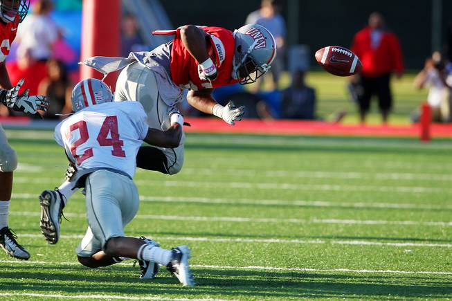 UNLV running back Adonis Smith loses the ball after being hit by Fred Wilson during their spring football game Friday, April 12, 2013.