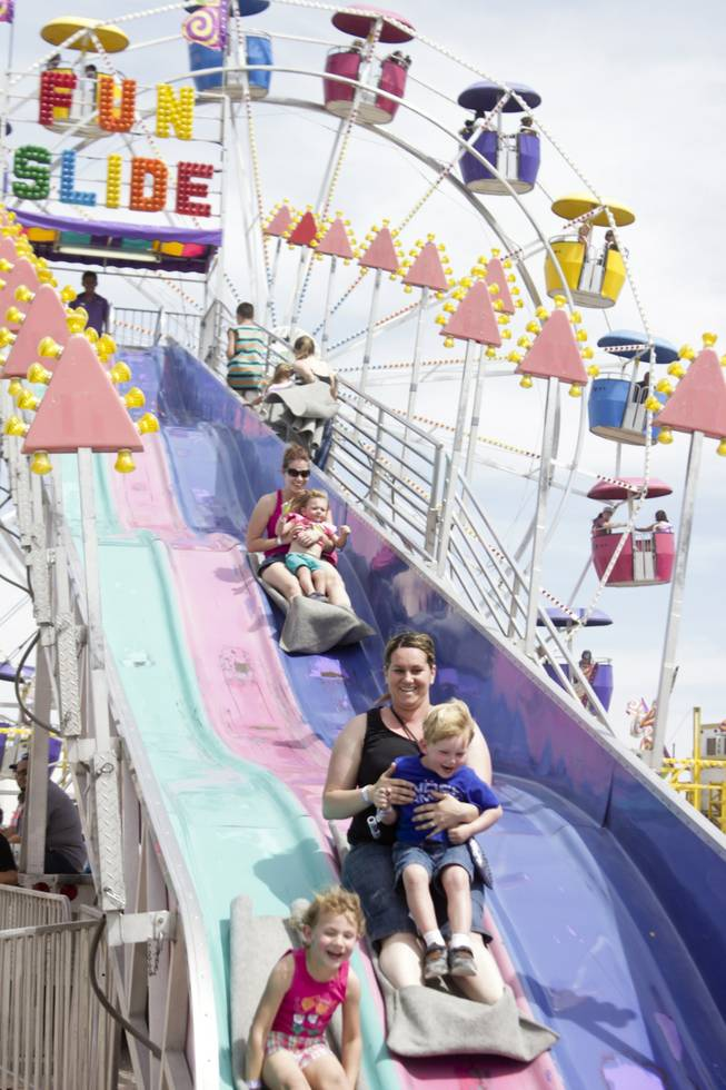 Fair-goers race down the Fun Slide at the 2013 Clark County Fair, Saturday, April 13, 2013.