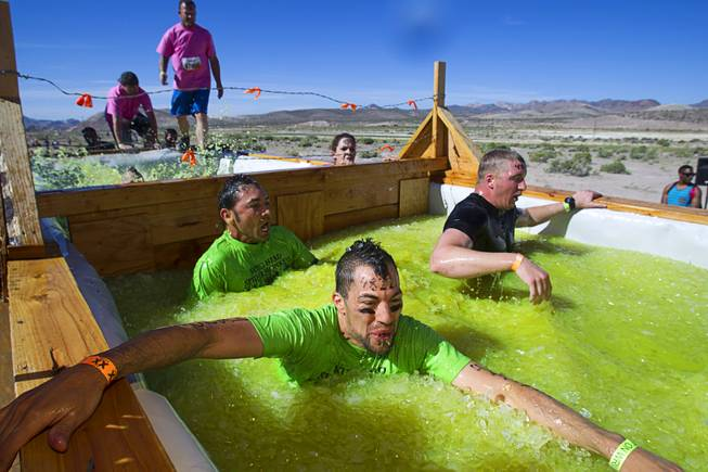 "Competitors make their way through the ""Arctic Enema"" during the Tough Mudder in Beatty, Nev. Sunday, April 14, 2013. Tough Mudder events are hardcore 10-12 mile obstacle courses designed to test all-around strength, stamina, mental grit, and camaraderie."