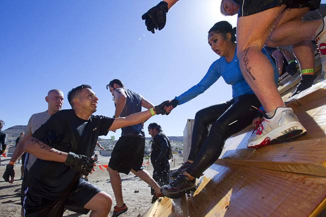 A man assists a companion during the Tough Mudder in Beatty, Nev. Sunday, April 14, 2013. Tough Mudder events are hardcore 10-12 mile obstacle courses designed to test all-around strength, stamina, mental grit, and camaraderie.