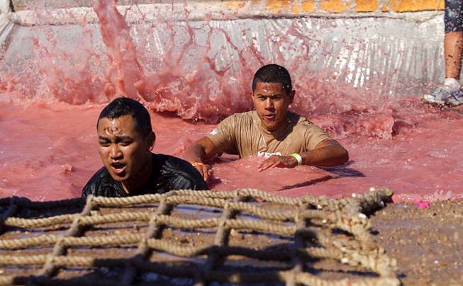 "Competitors make their way through the ""Firewalker"" obstacle during the Tough Mudder in Beatty, Nev. Sunday, April 14, 2013. Tough Mudder events are hardcore 10-12 mile obstacle courses designed to test all-around strength, stamina, mental grit, and camaraderie."