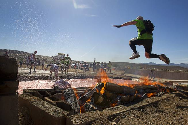 A man leaps over fire into a water pit during the Tough Mudder in Beatty, Nev. Sunday, April 14, 2013. Tough Mudder events are hardcore 10-12 mile obstacle courses designed to test all-around strength, stamina, mental grit, and camaraderie.