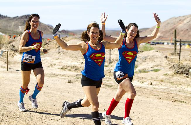 Women with matching Superman shirts start off during the Tough Mudder in Beatty, Nev. Sunday, April 14, 2013. Tough Mudder events are hardcore 10-12 mile obstacle courses designed to test all-around strength, stamina, mental grit, and camaraderie.