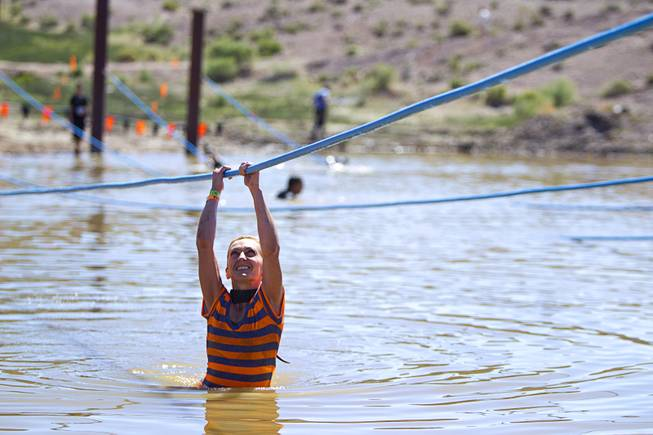 Mia Mijan of Las Vegas makes her way across an obstacle during the Tough Mudder in Beatty, Nev. Sunday, April 14, 2013. Tough Mudder events are hardcore 10-12 mile obstacle courses designed to test all-around strength, stamina, mental grit, and camaraderie.