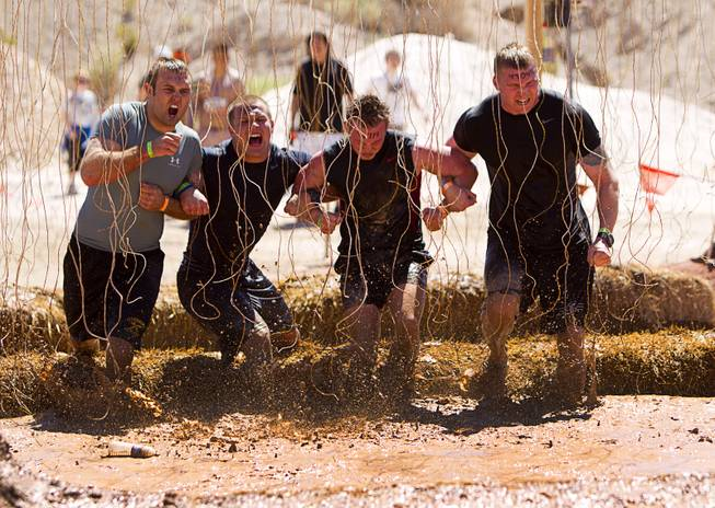 "A group gets shocked by live wires in the ""Electroshock Therapy"" obstacle during the Tough Mudder in Beatty, Nev. Sunday, April 14, 2013. Tough Mudder events are hardcore 10-12 mile obstacle courses designed to test all-around strength, stamina, mental grit, and camaraderie."