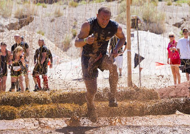 "A man runs through live wires in the ""Electroshock Therapy"" obstacle during the Tough Mudder in Beatty, Nev. Sunday, April 14, 2013. Tough Mudder events are hardcore 10-12 mile obstacle courses designed to test all-around strength, stamina, mental grit, and camaraderie."
