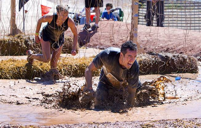 "Kimberly Pettit and James Russell of Las Vegas make their way though the ""Electroshock Therapy"" obstacle during the Tough Mudder in Beatty, Nev. Sunday, April 14, 2013. Tough Mudder events are hardcore 10-12 mile obstacle courses designed to test all-around strength, stamina, mental grit, and camaraderie."