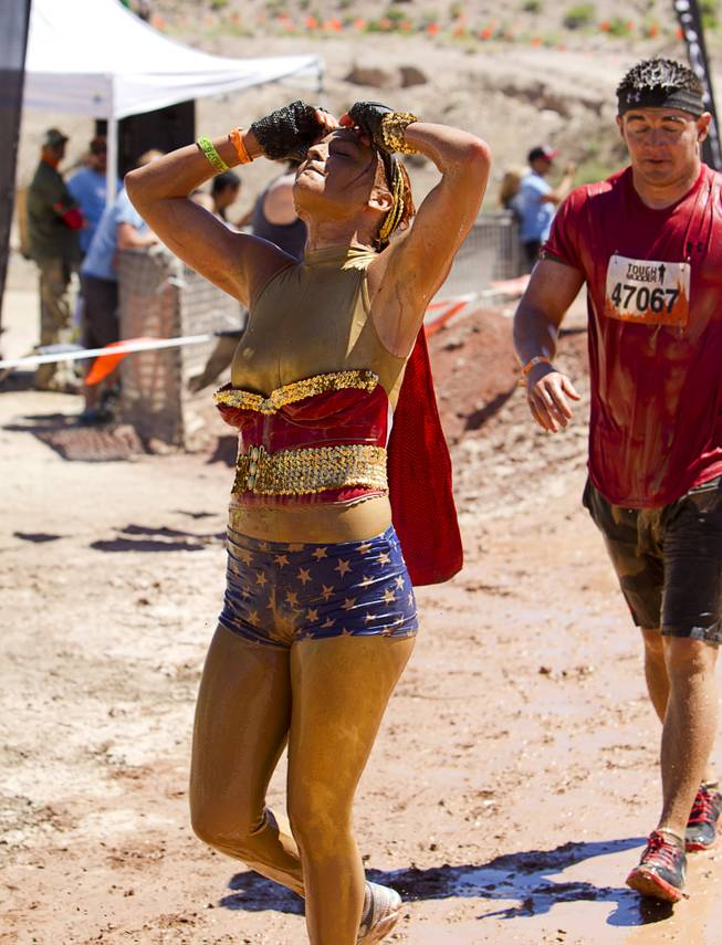 Kali Jones of Las Vegas, dressed as Wonderwoman, crosses the finish line during the Tough Mudder in Beatty, Nev. Sunday, April 14, 2013. Tough Mudder events are hardcore 10-12 mile obstacle courses designed to test all-around strength, stamina, mental grit, and camaraderie.