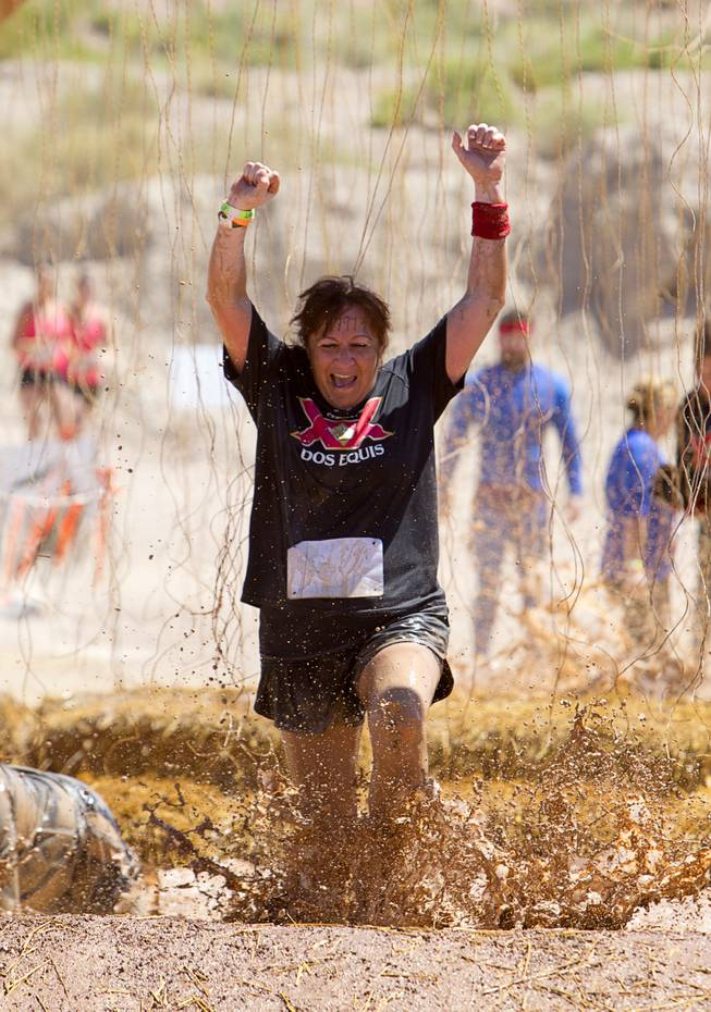 "Gabrielle Cummings of Las Vegas celebrates as she makes it through the ""Electroshock Therapy"" obstacle during the Tough Mudder in Beatty, Nev. Sunday, April 14, 2013. Tough Mudder events are hardcore 10-12 mile obstacle courses designed to test all-around strength, stamina, mental grit, and camaraderie."