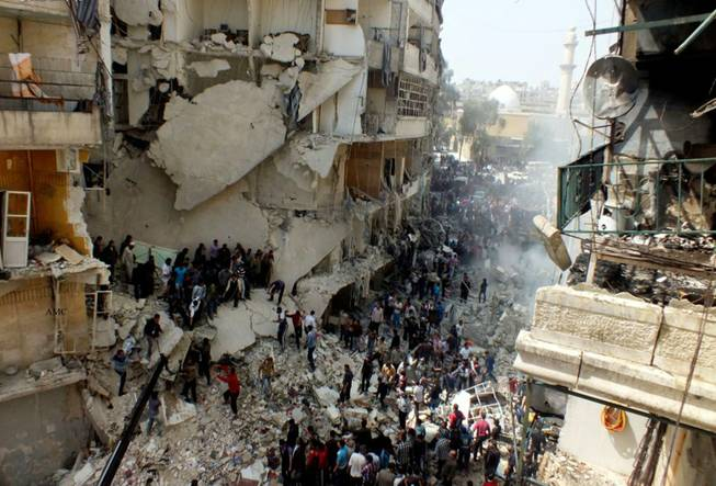 This citizen journalism image taken on Sunday, April 7, 2013, and provided by Aleppo Media Center AMC, which has been authenticated based on its contents and other AP reporting, shows Syrian citizens searching for bodies in the rubble of damaged buildings that were attacked by Syrian forces airstrikes, in the al-Ansari neighborhood of Aleppo, Syria. More than 70,000 people have died since Syria's crisis erupted in March 2011. The Syria-based Violations Documentation Center says nearly 9,000 government troops have been killed in two years of fighting between President Bashar Assad's forces and rebels trying to topple him.