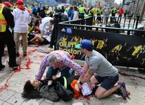 An injured woman is tended to at the finish line of the Boston Marathon, in Boston, Monday, April 15, 2013. Two explosions shattered the euphoria ...