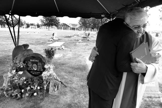 The Rev. Julio Alberto Alzate hugs Arturo Martinez-Sanchez after blessing the headstone at the gravesite of Yadira and Karla Martinez on April 16, 2013, at Woodlawn Cemetery in Las Vegas.