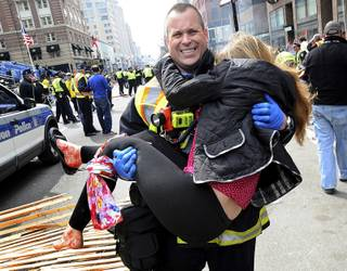 In this Monday, April 15, 2013 photo, Boston Firefighter James Plourde carries an injured girl away from the scene after a bombing near the finish line of the Boston Marathon in Boston. The FBI's investigation into the bombings at the Boston Marathon was in full swing Tuesday, with authorities serving a warrant on a suburban Boston home and appealing for any private video, audio and still images of the blasts that killed at least three and wounded more than 170.