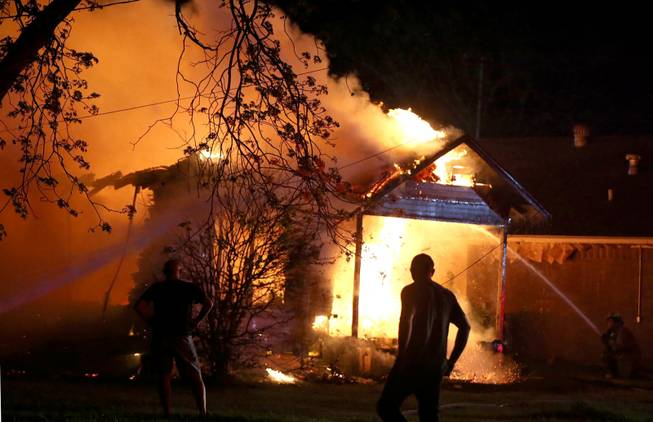 A person looks on as emergency workers fight a house fire after a near by fertilizer plant exploded Wednesday, April 17, 2013, in West, Texas.
