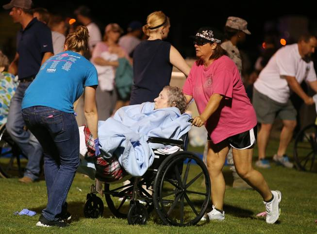 An elderly person is assisted at a staging area at a local school stadium following an explosion at a fertilizer plant Wednesday, April 17, 2013, in West, Texas. An explosion at a fertilizer plant near Waco caused numerous injuries and sent flames shooting high into the night sky on Wednesday.