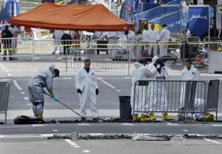 People in protective suits rake and examine material on Boylston Street in Boston Thursday, April 18, 2013 as investigation of the Boston Marathon bombings continues.