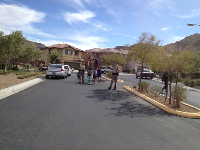 Children coming home from school are escorted by a police officer to their home near a crime scene where two children and a woman were found dead on Natures Glen Ave., and Jade River Lane on Friday, April 19, 2013.