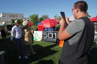 Kenny Keys jokes around with Mojave Max, the mascot for the Clark County Desert Conservation Program, while Aleks Vekic takes their photo during GreenFest at UNLV Saturday, April 20, 2013.