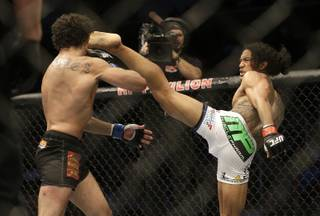 Benson Henderson, right, kicks Gilbert Melendez during the second round of a UFC lightweight championship mixed martial arts fight in San Jose, Calif., Saturday, April 20, 2013. Henderson won by split decision to retain the championship. (AP Photo/Jeff Chiu)