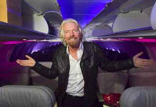 Sir Richard Branson, Virgin Group founder, poses inside a Virgin America jet as he celebrates the new Virgin America service between Los Angeles and Las Vegas after the arrival of the inaugural flight at McCarran International Airport on Monday, April 22, 2013.