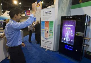 Steve Orlando of Phoenix plays a game on a vending machine equipped with XBox Kinect technology at a Pepsico booth during the NAMA (National Automatic Merchandising Association) One Show at the Sands Expo Center Wednesday, April 25, 2013. The NAMA One Show convention serves the vending, coffee and food service industries.